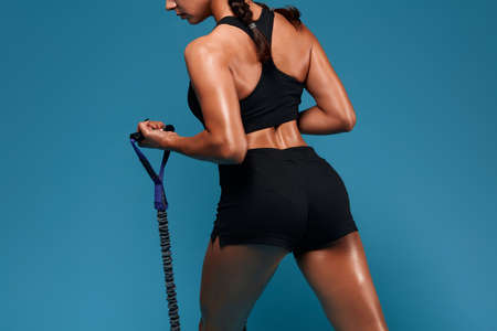 woman using expander, sport equipment during training, girl with sexy butt training at gym. close up cropped back view photo,isolated blue background, Stok Fotoğraf