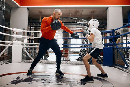 young boxer training with his coach at sport club, full length photo. hobby, interest concept Stock fotó