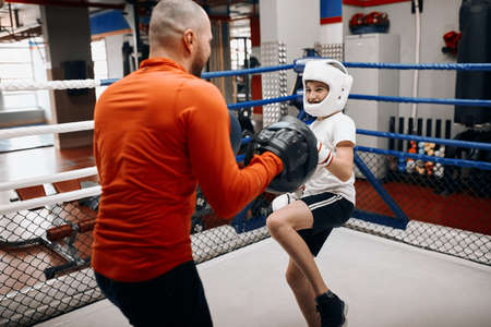 boy developing kicking drills, punching routines, close up photo.young boxer performing some exercises with raised leg