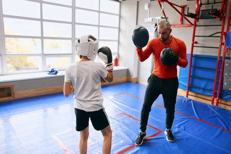 professional talented coach teaching a boy to box, close p photo. education, back view photo