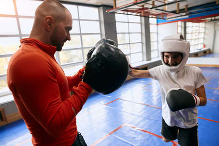 little boy gets pleasure from boxing workout, close up side view photo. pastime, leisure
