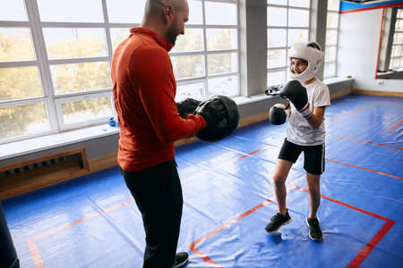 young boxer having fun with his coach at sport club. close up photo Reklamní fotografie