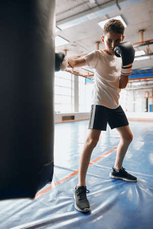 young boxer learns to hit the heavy bag at gym, full length photo. advertisement of boxing club, straight blow, boy trying to acieve big goals in boxing Reklamní fotografie