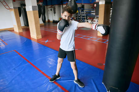 child working out with heavy punch bag, full length photo.