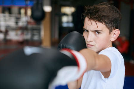 agressive angry boy punching with boxing gloves.close up cropped photo. blurred foreground.