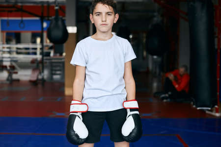 young boxer in fashion sportswear and gloves looking at the camera, free time, spare time, close up photo
