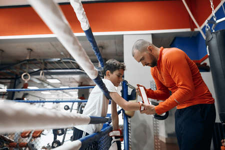 coach helping boy to prepare for boxing. close up side view photo.lifestyle , hobby, interest Reklamní fotografie