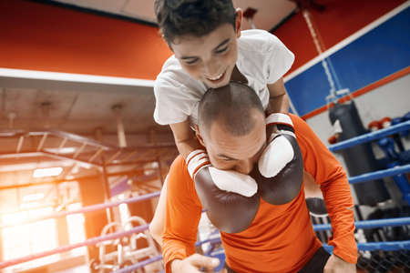 funny happy boy in boxing gloves holding his dads neck while fighting with him, happiness. happpy fatherhood, parenthood. close up photo Zdjęcie Seryjne