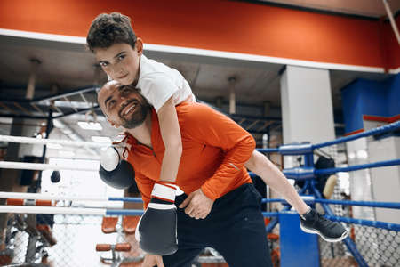 cheerful young bearded man giving piggyback ride to smiling kid in boxing gloves at gym, free time, spare time, lifestyle