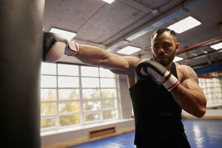 hardworking man learning to knock down the opponent at gym close up photo. guy hits heavy bag indoors