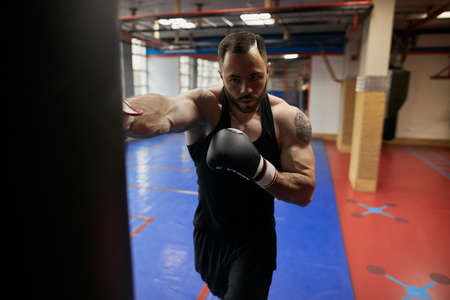 sportsman delivers a blow on punching bag, close up photo.strength training Reklamní fotografie