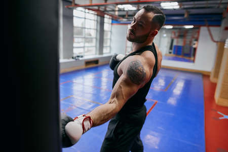serious boxer with tatoo on his arm spending time at gym. close up photo. leisure concept