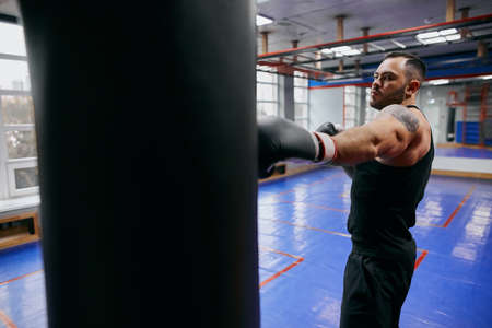 agressive angry fighter reducing stress at gym. close up side view photo. Reklamní fotografie