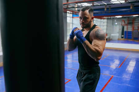young serious strong man concentrated on boxing, warming up before training. self-defense.protection