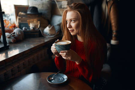 gorgeous good looking girl in stylish sweater having a rest , sitting at the table with her favourite coffee, relaxation, close up photo. girl with latte looking at the window, waiting for her friend
