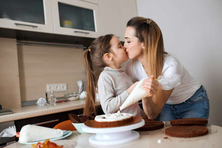 mother and her adorable daughter kissing each other, holding pastry bag in hands. love, family , relationship. close up side view photo