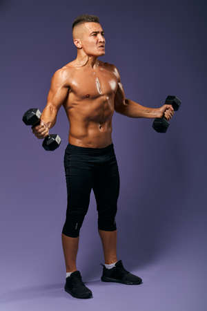 agressive tired sweaty man is keen on bodybuilding, full length side view photo. isolated blue background, studio shot
