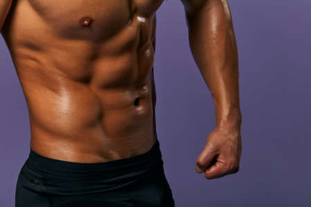 Cropped image of fit slim man showing six pack abs. close up side view photo. body care, beauty concept, motivation, result of effective training. isolated blue background