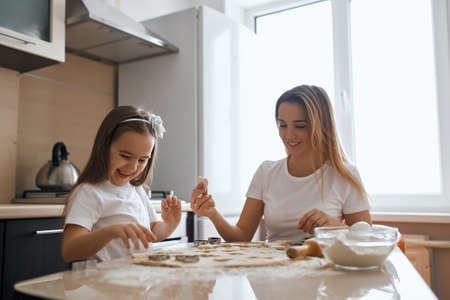 cheerful smiling woman and her daughter making cookies. close up photo. happiness. best time with mommy, positive atmosphere, mood at home