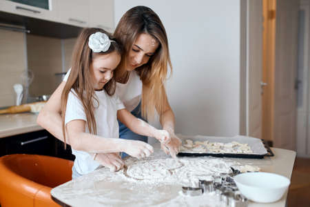 happy mommy teaching her daughter to draw a heart on the table with spilled flour. close up side view photo.creative art, Stockfoto