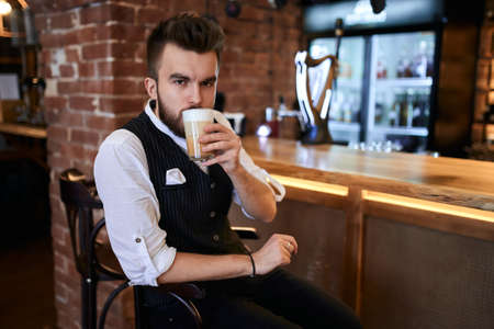 serious young man in elegant clothes drinking new sort of coffee, aroma which is not resisted by a barmen