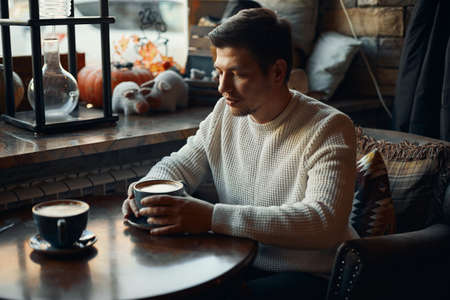 sad unhappy man is sitting at the table, he has argumnet with his girlfriend, problems in family. close up side view photo. hopeless love 版權商用圖片