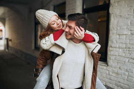 childish behavior, young positive attractive girl flirting with her boyfriend outdoors , close up photo