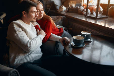 yong beautiful woman with closed eyes leaning on her mans shoulder while drinking tea indoors. close up side view photo,. best time with family, husband. 版權商用圖片