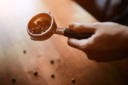 man holding portafilter with coffee beans, close up cropped photo 版權商用圖片