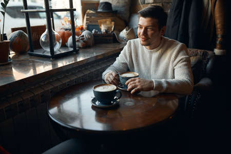 Young handsome thoughtful pensive man with a cup of coffee waiting for his girlfriend, close up photo, beauty, love, date