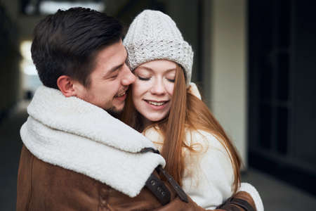 Happy young couple in stylish warm coats hugging on city street. close up photo. tenderness, love, positive feeling and emotion