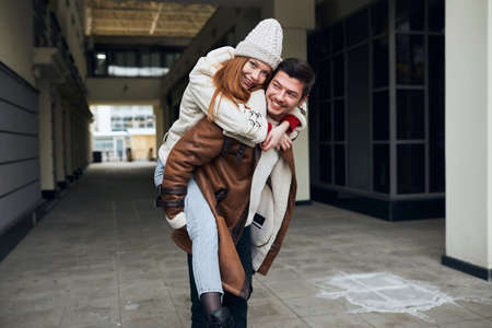 cheerful awesome guy giving piggyback ride to girlfriend, having fun in the city. close up portrait, love story