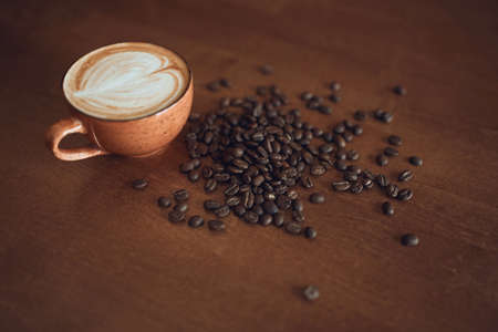 Composition with white cup of coffee and many beens is on the wooden table of the coffee shop, top view photo.coffee lover 版權商用圖片