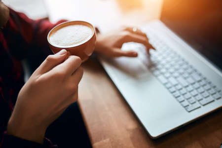 Man in cafe using laptop to chat and play social media and drinking hot coffee.close up cropped side view photo. male hands with coffee cup , man sitting at workplace and tasting yummy coffee 版權商用圖片