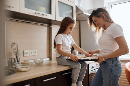 beautiful blonde mother and daughter baking cookies together, holding tray of raw cookie dough, hobby, lifestyle, free time, spare time. close up side view photo 版權商用圖片