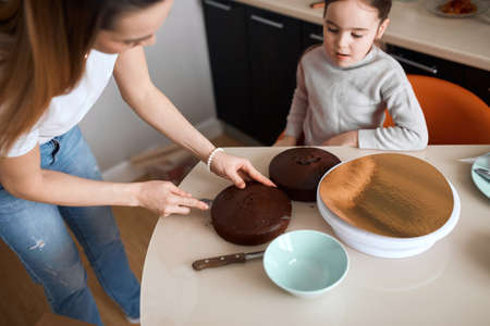 beautiful mom and daughter are preparing birthday cake together, mom is cutting sponge cake using knife in kitchen.top view angle . cropped photo. lifestyle, free time, spare time