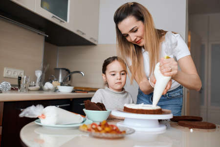 young attractive woman putting cream on the top of cake, little curious cute girl watching it, close up photo. family tradition, free time activity, first helper