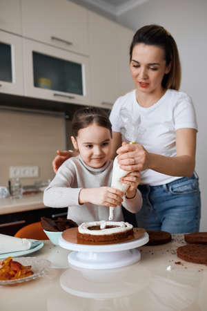 smiling adorable girl concentrated on toppig sponge, kid going to become a chef, cook, confectioner. closup photo. enjoyment, entertainment