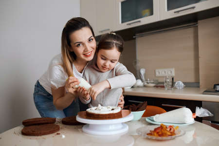 little girl wants to be a successful confectioner, woman and girl squeezing whipped cream on sponge, close up photo