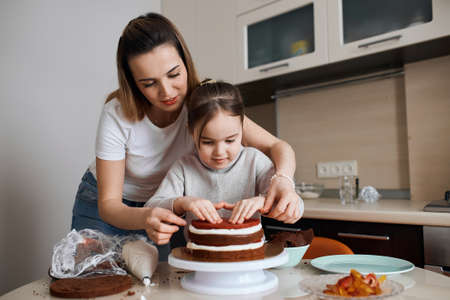 young good looking woman teaching child to make dessert, kid is fond of cooking with mother, hobby 版權商用圖片