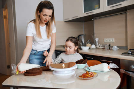 little cute girl and her mother baking cake for daddy, new year, fathers day, holiday, celebration. close up photo