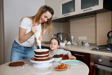 Close shot of a woman and her kid frosting a cake with whipped cream, close up photo, woman sharing cooking secrets with her daughter