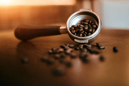 porta filter with roasted beans on a wooden table, close up photo, blurred foreground 版權商用圖片