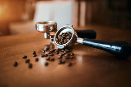 filter with grind beans on a wooden brown table. Roasted coffee beans.blurred foreground