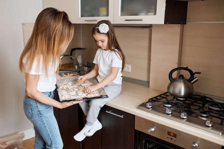 adorable awesome kid sitting on the kitchen table and laying out cookies on the baking tray, close up side view photo, copy space, challenge, copy space