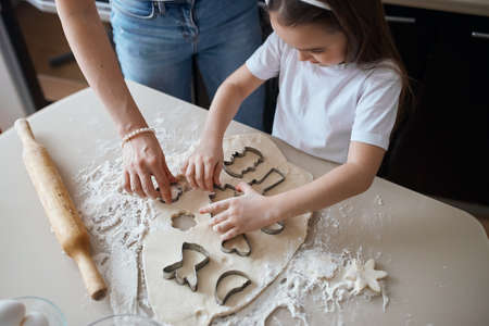 little girl making funny figures of cookies. close up top view cropped photo.