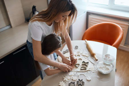 mother helping her kid to cut dough while cooking in the kitchen. close up top view photo. lifestyle, free time, spare time