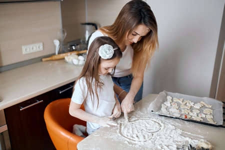 little cute girl spending great time with her mommy in the kitchen. close up side view photo.