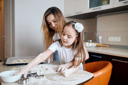 mother sprinkling flour on the dough for cookies while daughter playing with dough. close up photo.kid drawing something on the table with finger in the kitchen