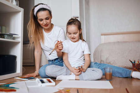 Happy family. Mother and daughter having drawing lesson at home, close up photo, firts experience as artist